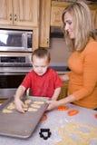 Femme et garçon effectuant des biscuits de Veille de la toussaint Images libres de droits