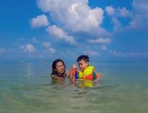 Femme et garçon utilisant un gilet de sauvetage, plongée à l'air en mer images stock