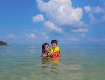 Femme et garçon utilisant un gilet de sauvetage, plongée à l'air en mer images libres de droits