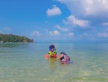 Femme et garçon utilisant un gilet de sauvetage, plongée à l'air en mer photo libre de droits