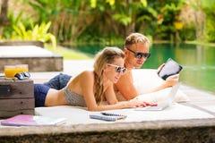 Femme et homme à l'aide des ordinateurs par la piscine Photos libres de droits