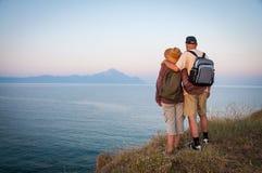 Femme et homme étreignant sur le dessus de la montagne dans le coucher du soleil Photo libre de droits
