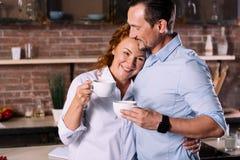 Femme et homme étreignant tout en buvant du café Photographie stock