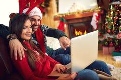Femme et homme appréciant avec l'ordinateur portable Images stock
