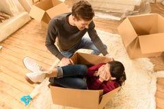 Femme et homme ayant l'amusement à la nouvelle maison Photographie stock libre de droits