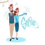 Femme et homme d'affaires prenant la photo de Selfie sur l'usage futé Santa Hat New Year Celebration de téléphone Photographie stock
