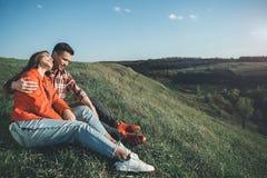 Femme et homme de sourire bondissant entre eux sur la colline Photographie stock libre de droits