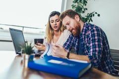 Femme et homme faisant des ?critures ensemble, ils rapportent l'imp?t en ligne photographie stock