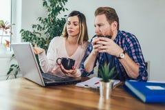 Femme et homme faisant des ?critures ensemble, ils rapportent l'imp?t en ligne photos libres de droits