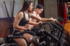 Femme et homme faisant du vélo dans le gymnase, exerçant des jambes faisant les vélos de recyclage de cardio- séance d'entraîneme Image stock