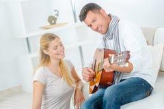 Femme et homme jouant la guitare dans le salon Image libre de droits