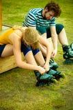 Femme et homme mettant sur des patins de rouleau Photographie stock libre de droits