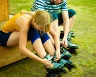 Femme et homme mettant sur des patins de rouleau Images libres de droits