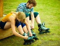 Femme et homme mettant sur des patins de rouleau Photographie stock