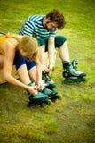 Femme et homme mettant sur des patins de rouleau Photos stock