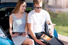 Femme et homme regardant le connecteur d'alimentation Photo stock