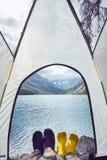 Femme et homme se situant dans la tente près du lac avec des vues de neige Photo stock
