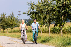 Femme et homme supérieurs à la visite de bicyclette Photos stock