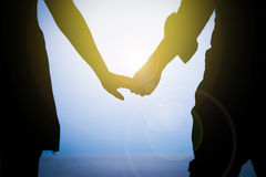 Femme et homme tenant la main avec le coucher du soleil Photographie stock