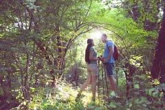 Femme et homme trimardant en montagnes avec le sac à dos Photos libres de droits