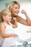 Femme et jeune fille dans des dents de brossage de salle de bains Images stock