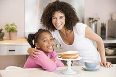Femme et jeune fille dans la cuisine avec le gâteau et le coff photographie stock libre de droits
