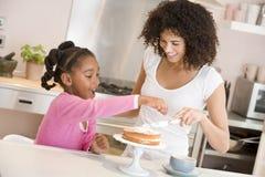 Femme et jeune fille dans la cuisine glaçant un smili de gâteau Photographie stock