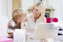 Femme et jeune garçon dans le Home Office avec l'ordinateur portatif Photo stock
