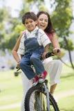 Femme et jeune garçon sur un vélo souriant à l'extérieur Photos libres de droits