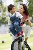 Femme et jeune garçon sur un vélo souriant à l'extérieur Photographie stock
