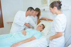 Femme et médecins avec à la salle d'hôpital photographie stock
