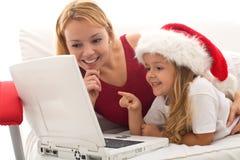 Femme et petite fille jouant sur un ordinateur portatif Photos libres de droits