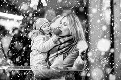 Femme et petite fille mangeant la pomme crystalized sur la marque de Noël Photographie stock libre de droits
