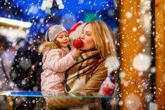 Femme et petite fille mangeant la pomme crystalized sur la marque de Noël Photos stock