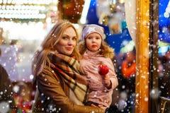 Femme et petite fille mangeant la pomme crystalized sur la marque de Noël Photo stock