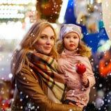 Femme et petite fille mangeant la pomme crystalized sur la marque de Noël Photos libres de droits