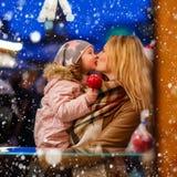 Femme et petite fille mangeant la pomme crystalized sur la marque de Noël Images stock