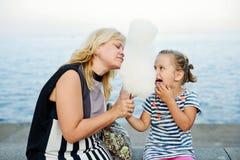 Femme et petite fille mangeant une sucrerie de coton Image stock