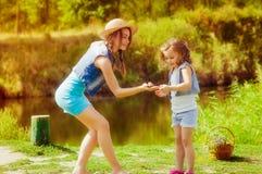 Femme et petite fille près de la rivière en automne avec une grenouille Photos libres de droits
