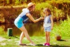 Femme et petite fille près de la rivière en automne avec une grenouille Image stock