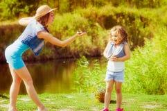 Femme et petite fille près de la rivière en automne avec une grenouille Photographie stock