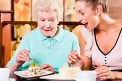Femme et petite-fille supérieures au café en café Image libre de droits