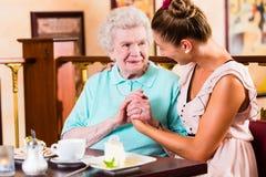 Femme et petite-fille supérieures au café en café Photo stock