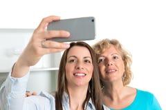 Femme et sa mère prenant un selfie ensemble dans la cuisine Images stock