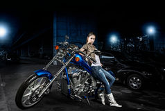 Femme et sa motocyclette dehors la nuit photographie stock libre de droits