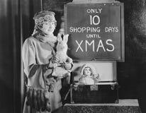 Femme et signe soucieux avec le nombre des jours d'achats jusqu'à ce que Noël (toutes les personnes représentées ne sont plus lon photos stock