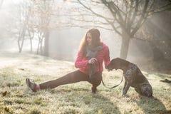 Femme et son étirage de chien extérieurs Fille de forme physique et son animal familier établissant ensemble Images libres de droits