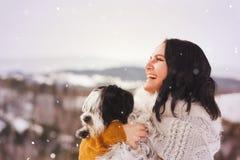 Femme et son chien de terrier tibétain un jour neigeux Images libres de droits