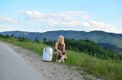 Femme et son chien par la route Photos libres de droits