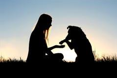 Femme et son chien se serrant la main la silhouette Photos libres de droits